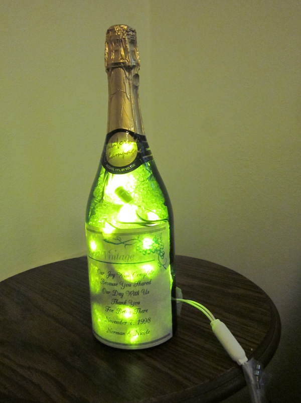 lighted wine bottle with holiday wreath and wine glass